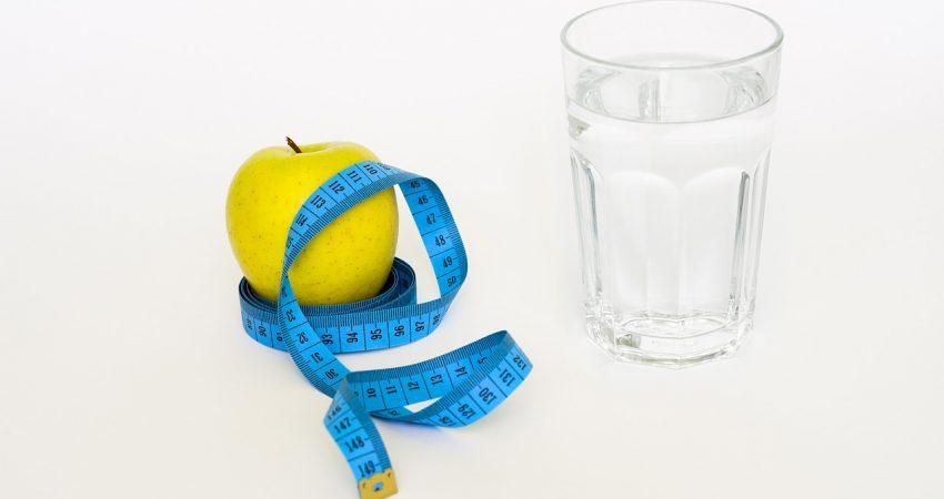 jabłko obok szklanki wody